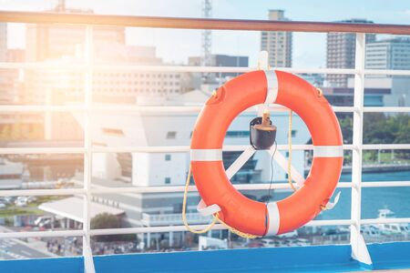 Orange lifebouy life loop on a ocean cruise ship for Sea and Ferry travel safety concept. Marine safety equipment on ship balcony.