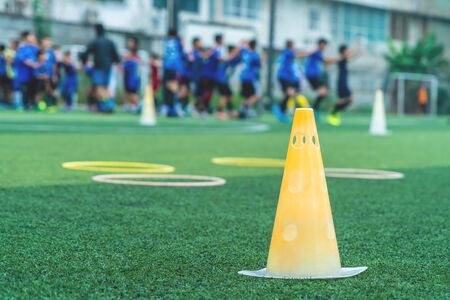 Soccer training equipment with cone and speed ring with football team training in the background
