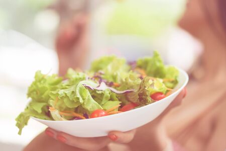 Blurred Woman holding a plate of Vegetable salad for healthy eating and healthy liffestyle concept.