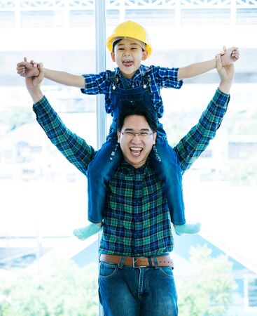 Father is holding his son on his shoulder with construction hat for family bonding concept.