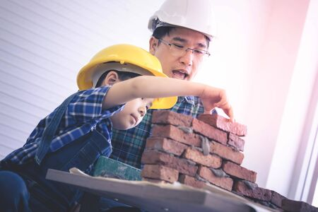 Builder Father is teaching his son on his profession as a construction worker and engineer brick layer