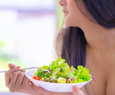 Healthy young woman is eating green salad for healthy lifestyle food concept Stok Fotoğraf