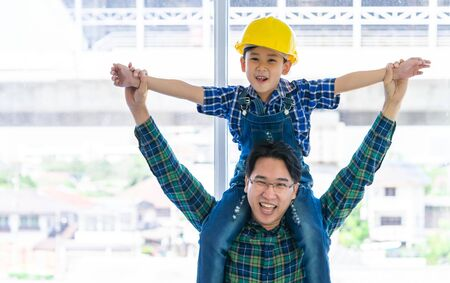 Father is holding his son on his shoulder with construction hat for family bo