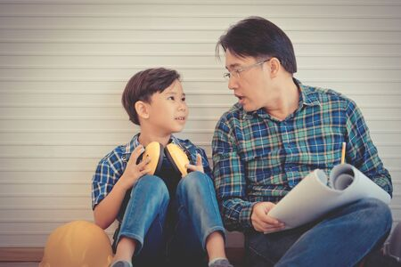 Builder Father is teaching his son to read the construction plan paper in vintage tone