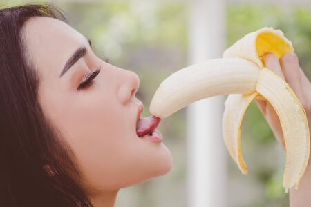 Asian woman is eating and licking the yellow banana for sensuality and temptation concept