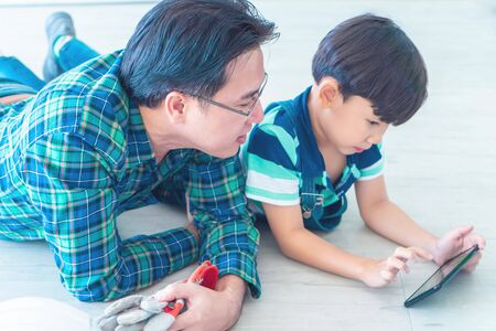 Father and son in using the smartphone together for modern family and parenting concept