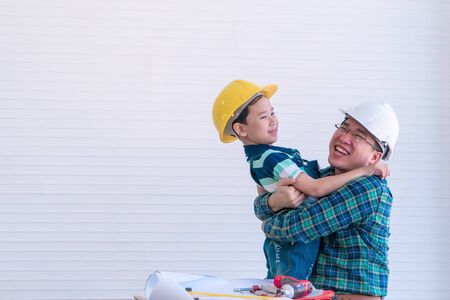 Father and son wearing construction suit is hugging while working in home improvement for family bonding and love concept.