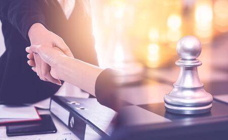 Geschäftsfrau macht einen Deal für Geld mit Chess Battle for Business Financial Handshake Success Deal Concept Standard-Bild