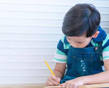 Asian boy is using pencil to wirting on wood for child education concept