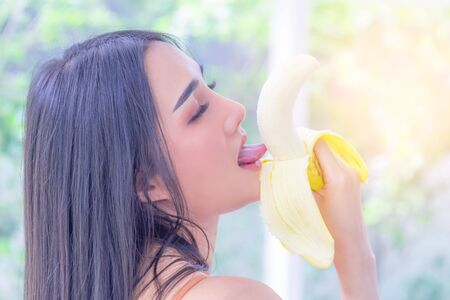 Woman is eating Banana for adult Sensuality concept.