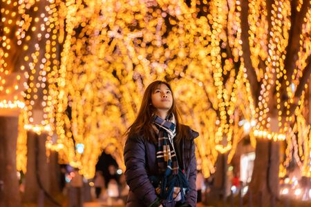 Beautiful Woman portrait in winter clothing at night in The Jozenji christmas light up festival in Sendai, Japan