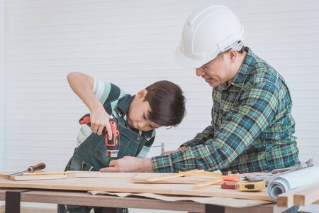 Father is teaching his son to fo the DIY home improvement work for parent and family bonding concept.