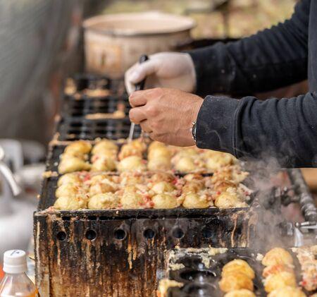 Seller is cooking Japanese Takoyaki Octopus Ball on a hot stove. Stock Photo