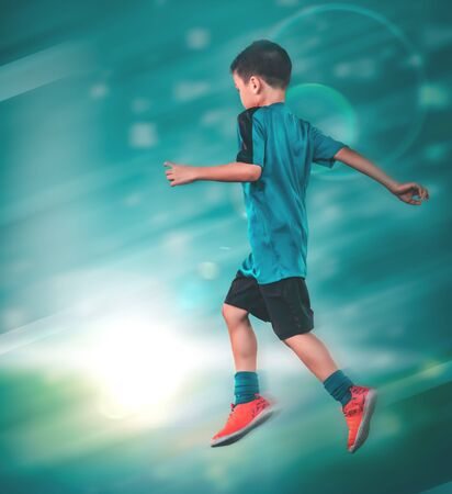 Little boy is kicking a soccer ball in sport training session with motion blur and light effect.