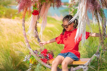 Asian kids are having a healthy time on an outdoor flower swing together, for children leisure and happiness freedom concept.