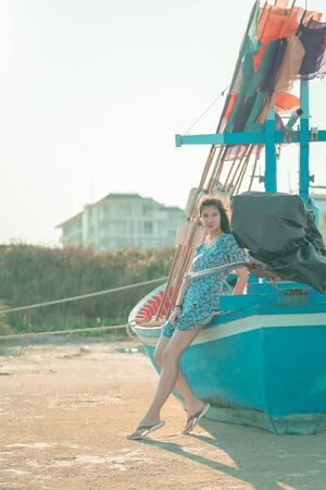 Beautiful Asian Chinese woman standing on a fishing boat side on a Thailand island beach