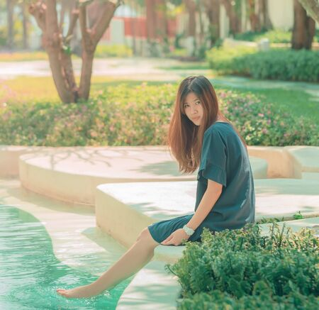 Asian Woman is relaxing in a summer resort garden and swimming pool for Summer Vacation Beach Travel concept. Foto de archivo