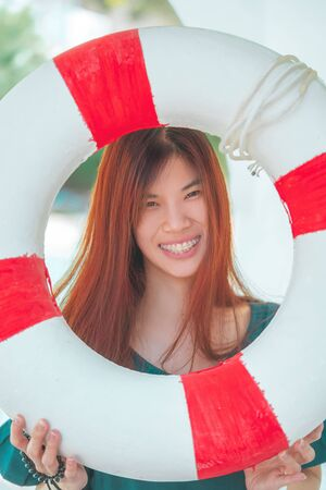 Happy Asian woman portrait with  life Buoy smile with happiness for happy summer beach vacation concept.