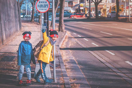 Sendai, Japan - 29 Dec 2019 : Two Japanese kids is waiting for school bus at Bus stop.