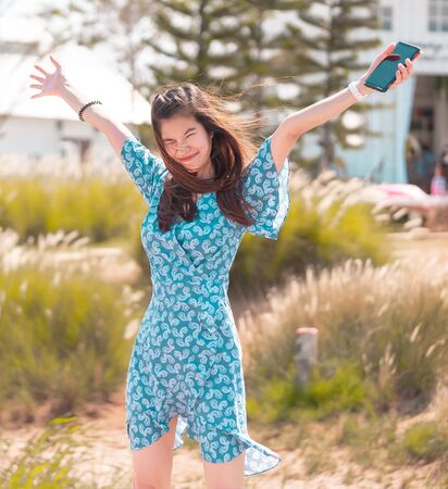 Asian girl putting her hand up to receive the summer hard wind blowing in the beauty body