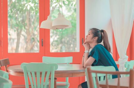 Asian woman sitting in a red cafe alone waiting for someone.