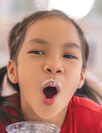 Girl is drinking a glass of milk with milk foam all over her mouth, for kid healthy eating concept.
