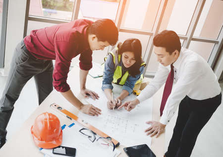 Construction team with business man engineer and architect is brainstorming on working table top view shot