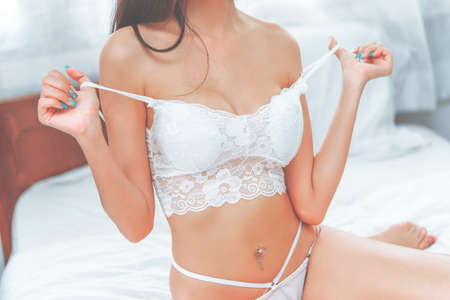 Seductive Asian woman is taking off white lingerie in her bedroom.