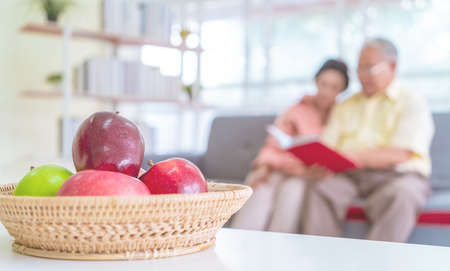 Happy retired asian couple reading book on a couch in living room with fresh fruit on the table to healthy eating and lifestyle concept.