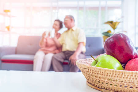 Happy retired asian couple reading book on a couch in living room with fresh fruit on the table to healthy eating and lifestyle concept. Standard-Bild
