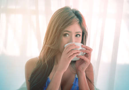 Asian female with sexy lingerie is drinking breakfast coffee in her bedroom. Фото со стока