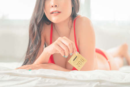 Seductive Woman is preparing her condom for protection before making love on the bed. Фото со стока