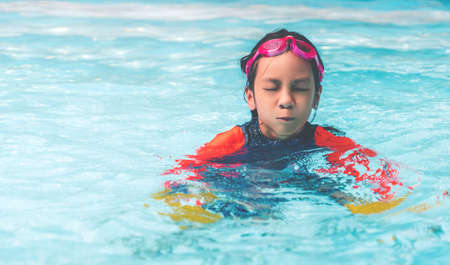 Asian girl is swimming with closed eyes in a swimming pool.