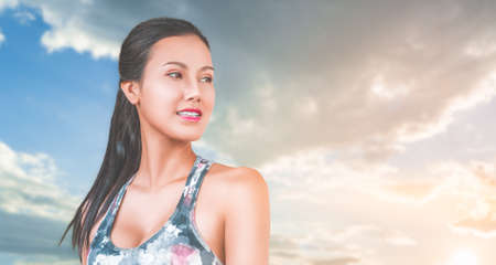 Active asian woman wearing sport bra portrait with Dramatic sky background.
