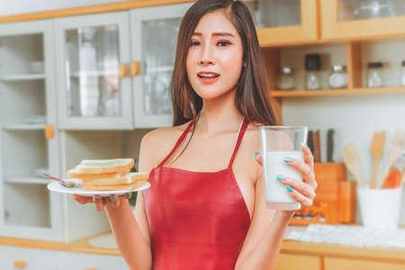 Happy Seductive girlfriend wearing only apron is preparing breakfast for her boyfriend.