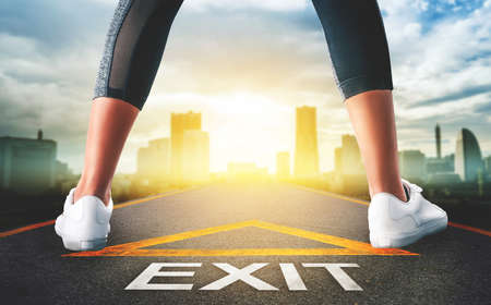 Woman standing on exit signage road for Business exit strategy concept with golden city skyline background.