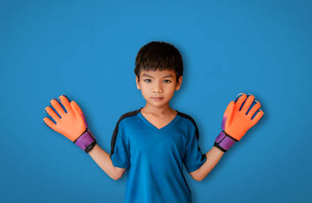 Asian boy is a football goalkeeper wearing gloves spreading his hand isolated on white.
