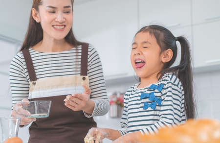 Asian little girl is disgust from the smell of Bakery ingredients as mother laughing in the background.