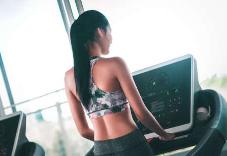 Woman is setting up before  start running on a treadmill, back view. Stok Fotoğraf