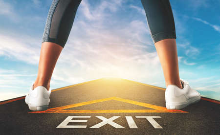 Woman standing on exit signage road for Business exit strategy concept with blue sky background.