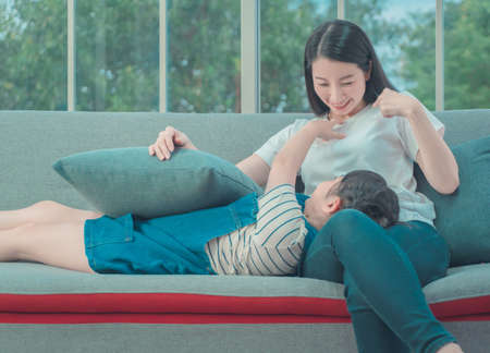 Asian Mother and daughter is playing together on Sofa at home for happy family lifestyle concept. Stock Photo