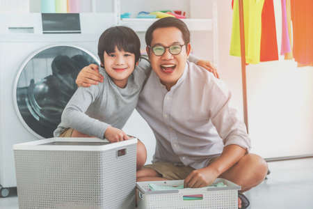 Happy Asian Father and son is smiling and laughing while doing laundry together at home for Family togetherness concept.