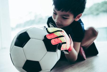 Kid soccer goalkeeper hand is catching a football closed up shot. 版權商用圖片