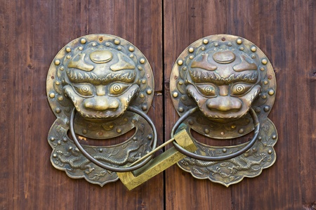 Chinese traditional lion knocker and phoenix lock on the door. Chinese believe these mythological beast can be protect their family and property. photo