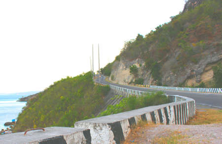 Ascending road on the hill beside the sea. Stock Photo