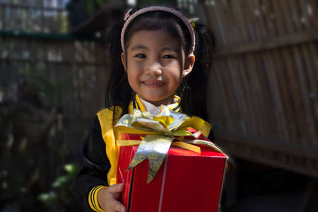 filipina: A little girl holding a gift. Stock Photo