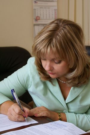 autograph: Serious business woman signing a document