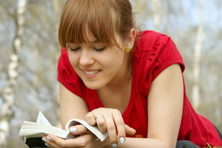 poems: Young girl lying with a book on spring grass in a park reading