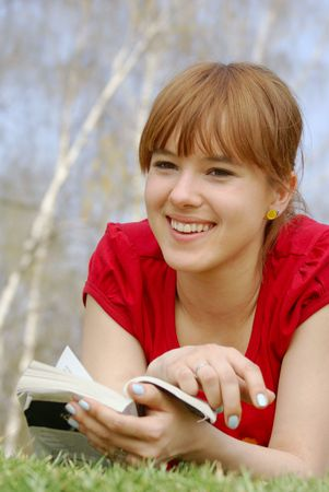 poems: Young girl lying with a book on spring grass in a park smiling                Stock Photo