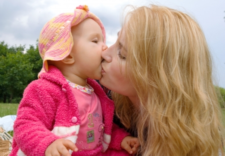 air kiss: Mom and daughter are kissing Stock Photo